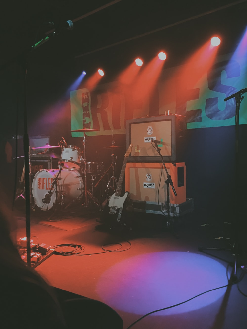 black and white electric guitar near speaker and drums