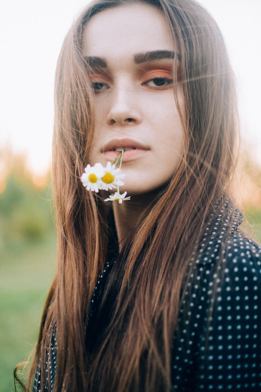 woman biting white daisy flower
