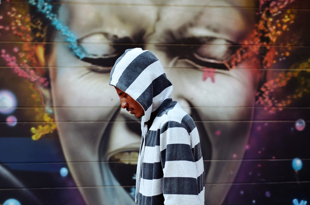 man wearing black and white striped hoodie standing near wall with graffiti of woman's face singing