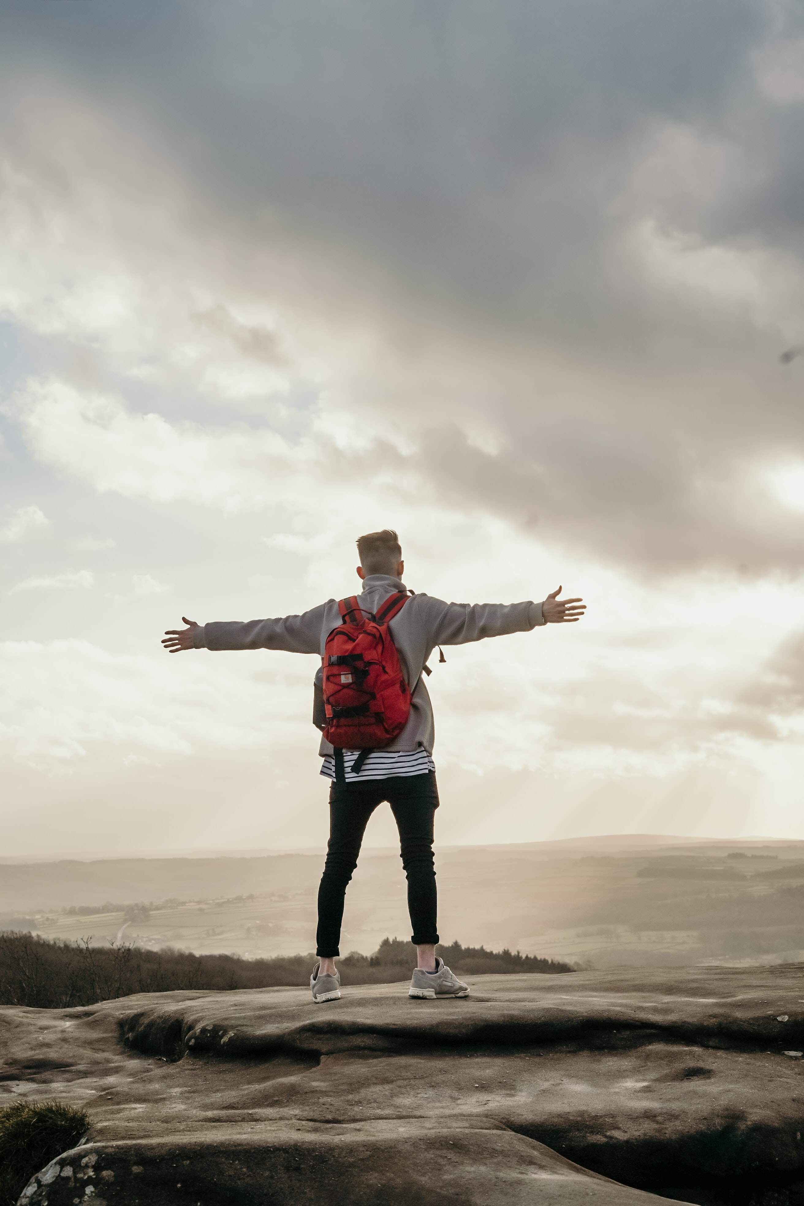 man spreading his arm wide while standing on top of hill