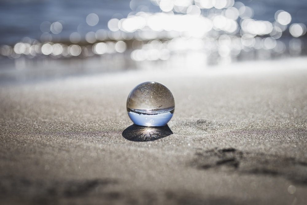 clear toy marble with reflection of seashore