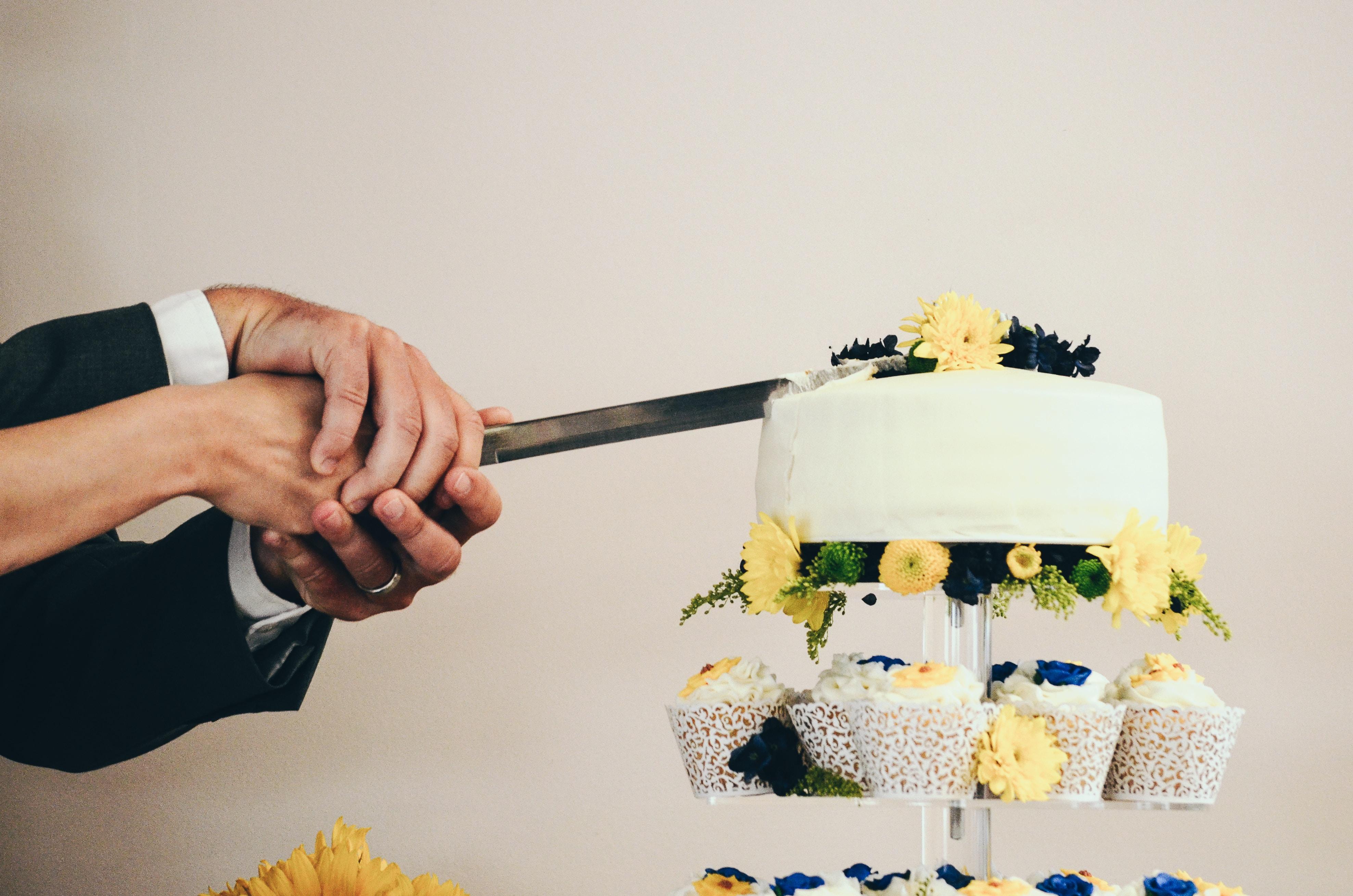 couple both holding knife slicing a cake on tray