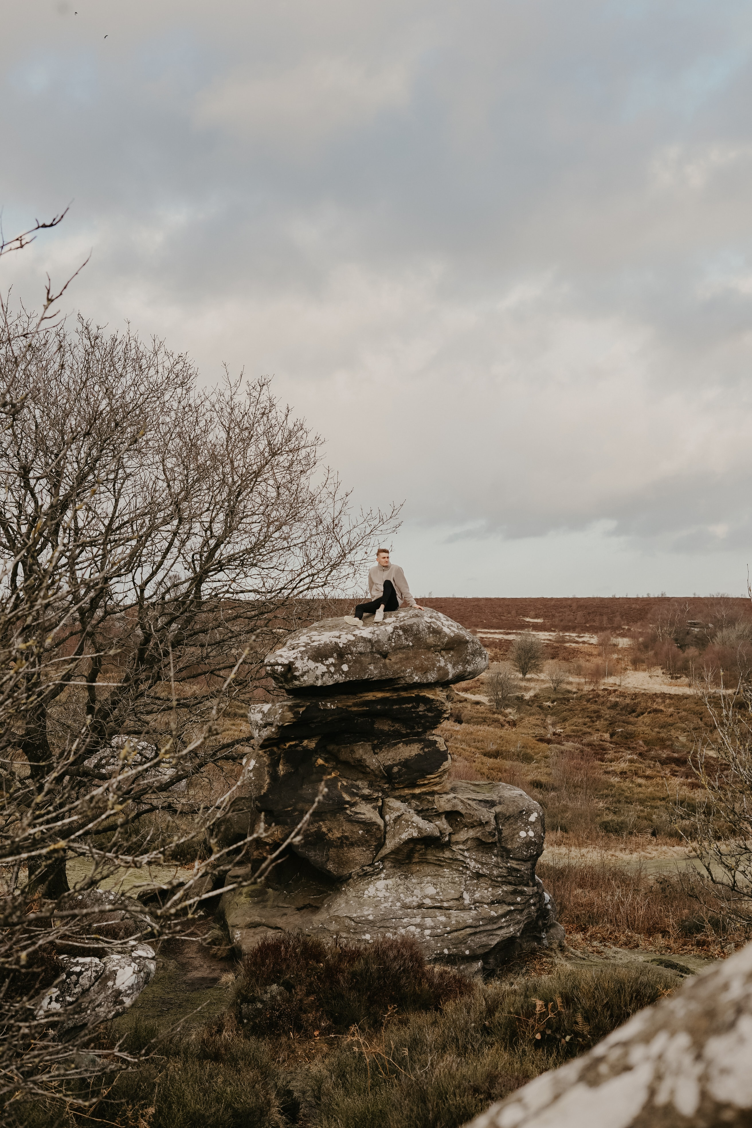 person sitting on piled rocks near trees during daytime