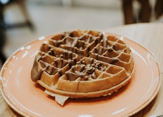 waffle on pink ceramic plate placed on wooden table