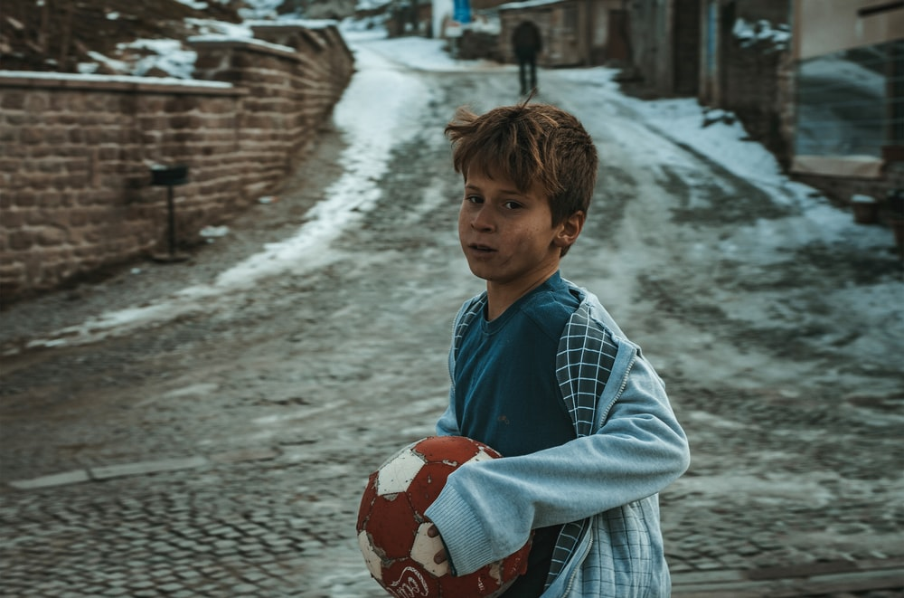 boy holding brown and white ball