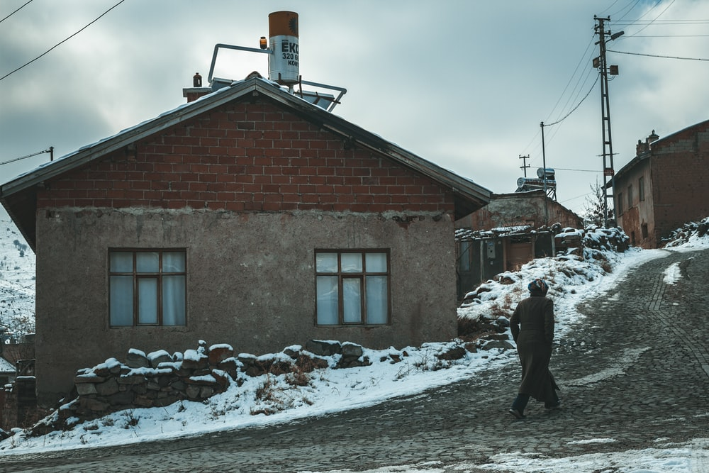 man walking beside gray and brown house during daytime