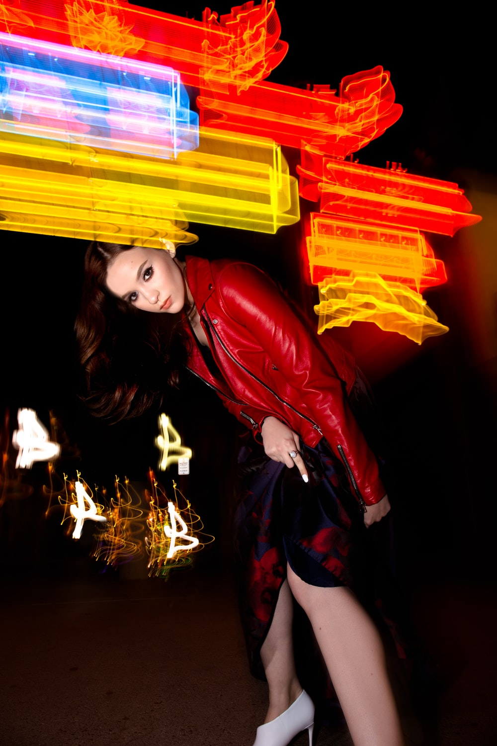 bokeh photography of woman in red leather jacket standing in dark space