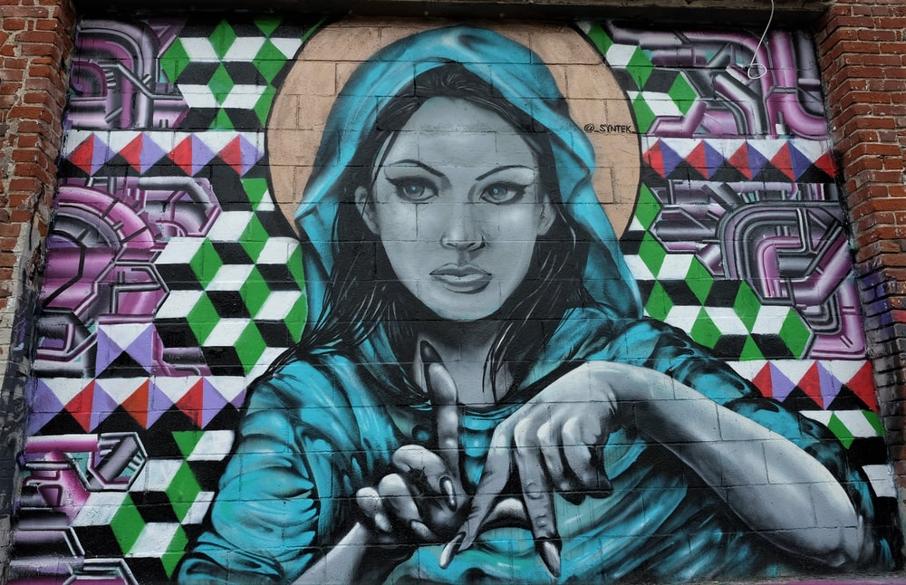 woman wearing hooded top making LA hand sign graffiti