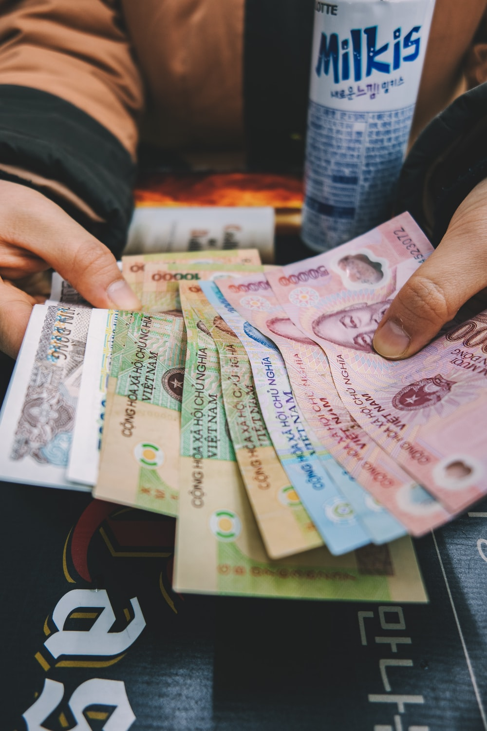 person holding assorted-amounts banknotes