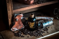 alchemy cold brew coffee bottle near the brown hatchet on brown wooden rack