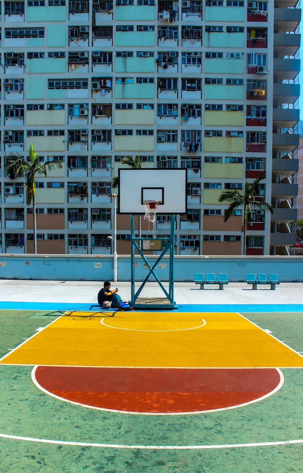 man sitting below basketball hoop near the building during daytime