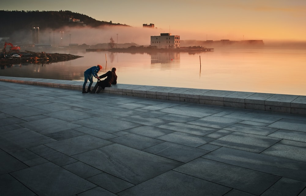 two person sitting on concrete floor near body of water during golden hour