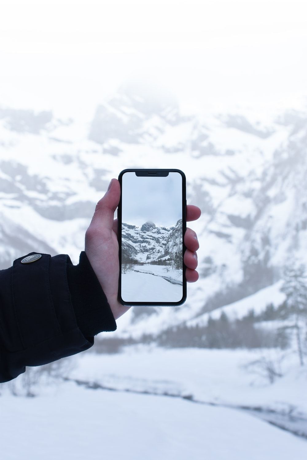 person taking picture at snow covered mountain
