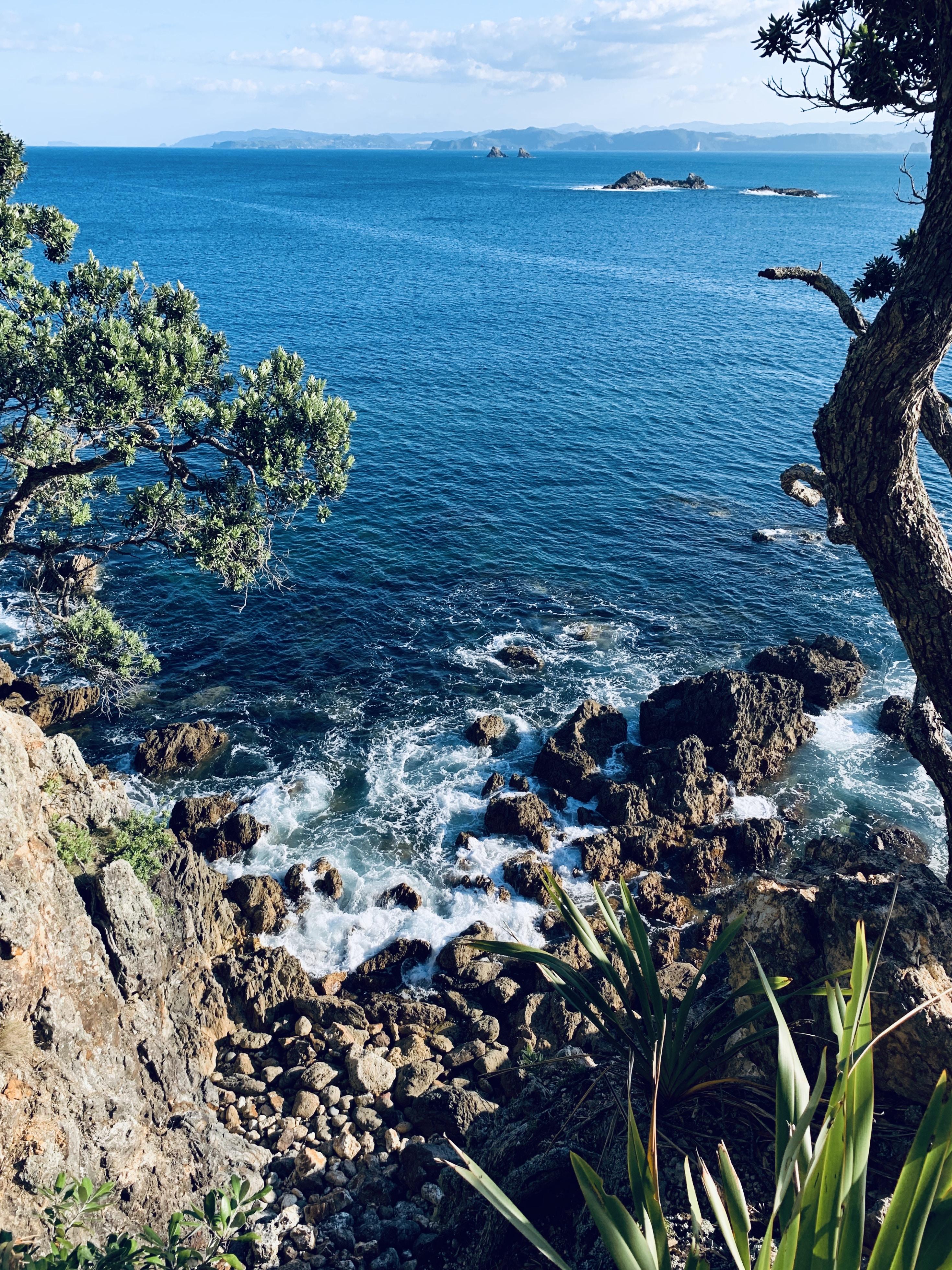 aerial photography of ocean water splashing to rocks during daytime