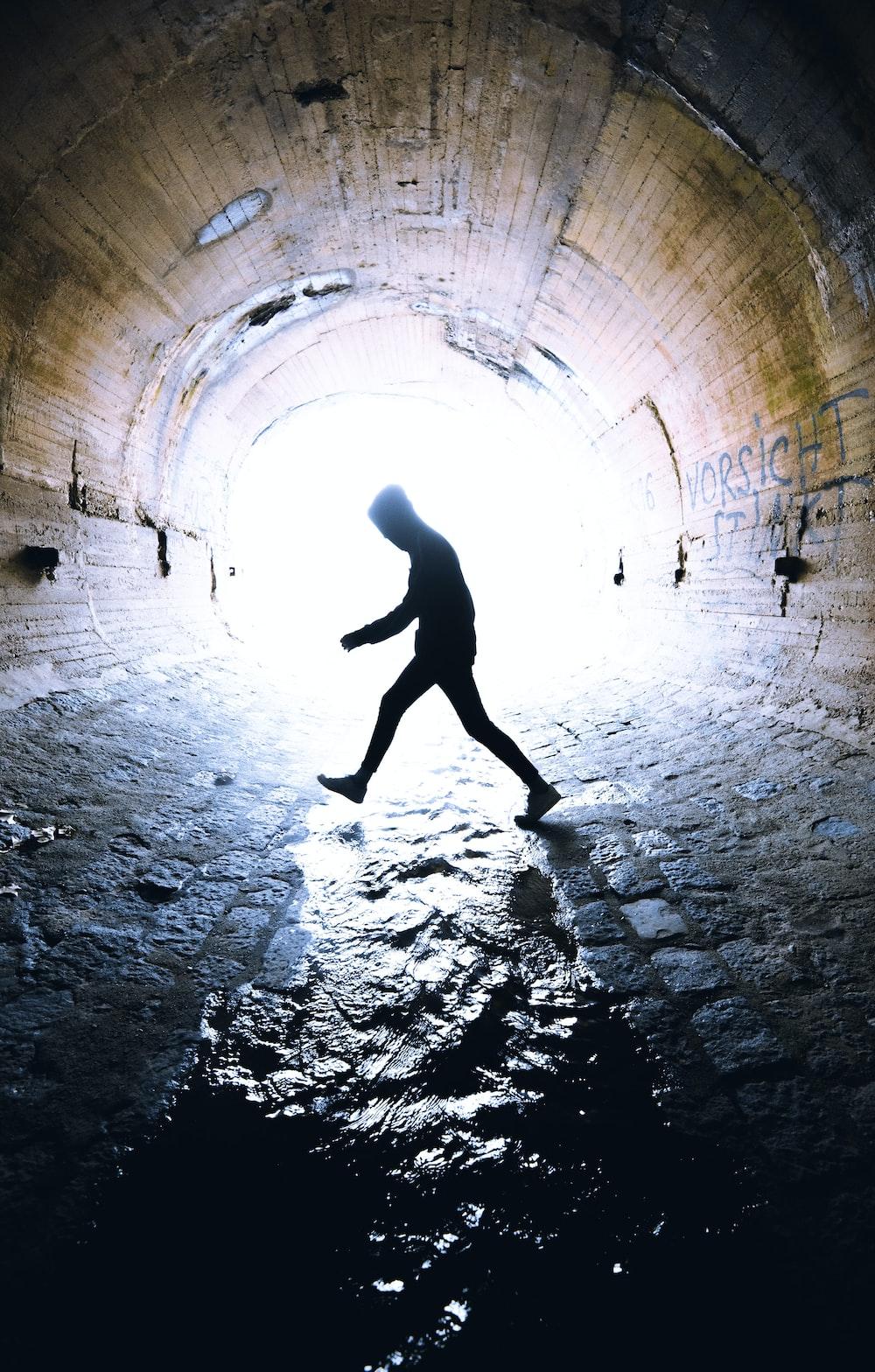 man walking inside tunnel during daytime