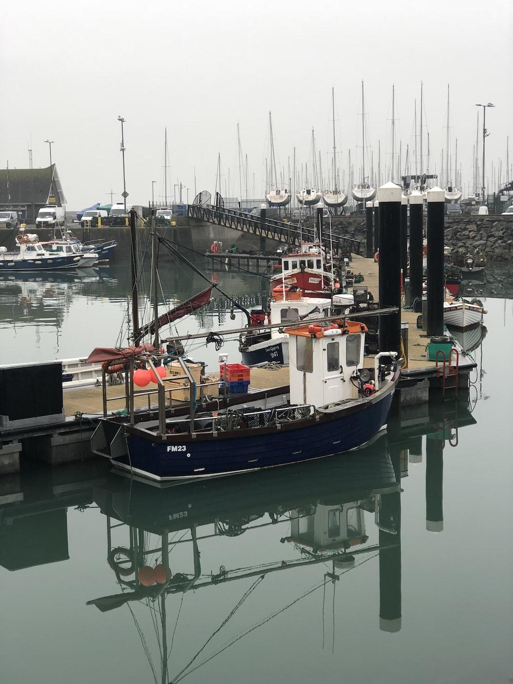 blue boat beside dock
