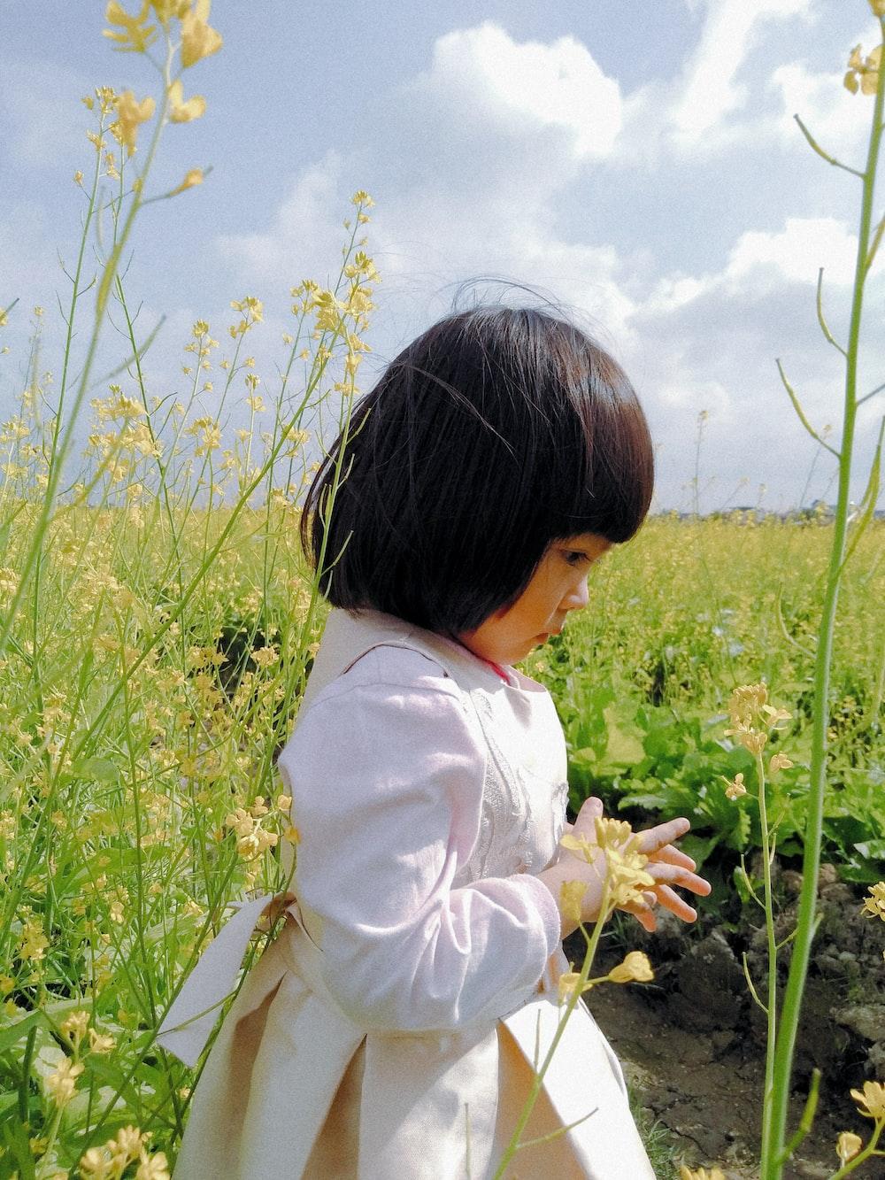 girl standing beside flowers