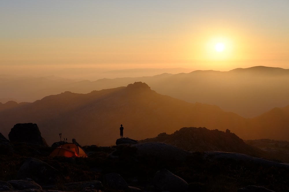 person standing on mountain near orange dome tent during sunrise