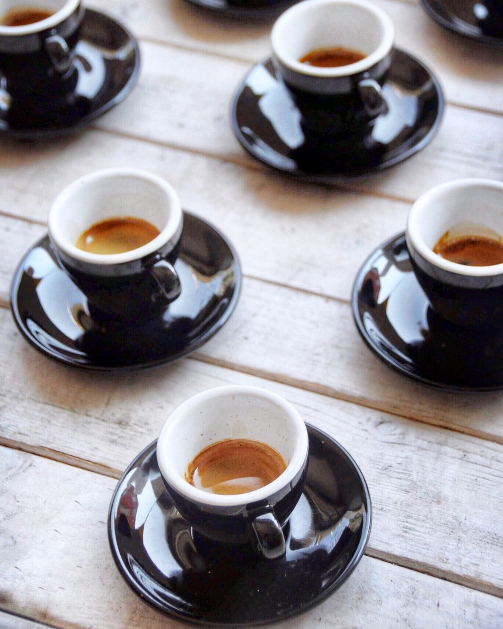 selective focus photography of four black-and-white ceramic cups and saucers