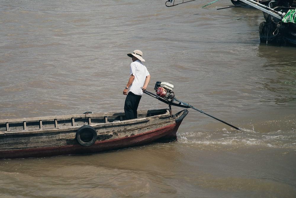 man in white t-shirt wearing hat riding speedboat
