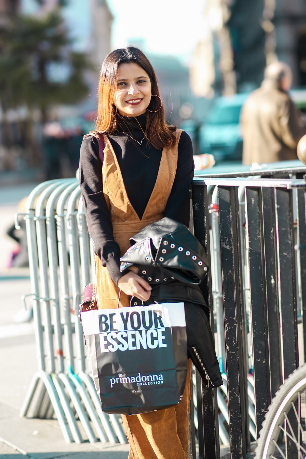 smiling woman holding black leather jacket and paper bag
