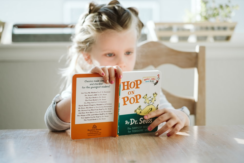 girl sitting while reading book