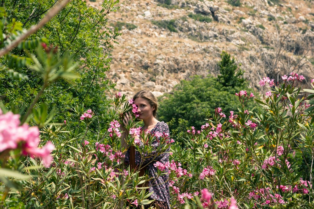 woman in black and pink floral dress standing surrounded with pink flowering plant during daytime