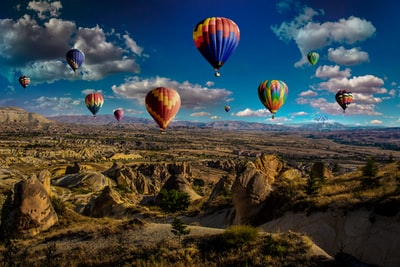 assorted-color hot air balloons over brown mountain range during daytime hot air balloon teams background