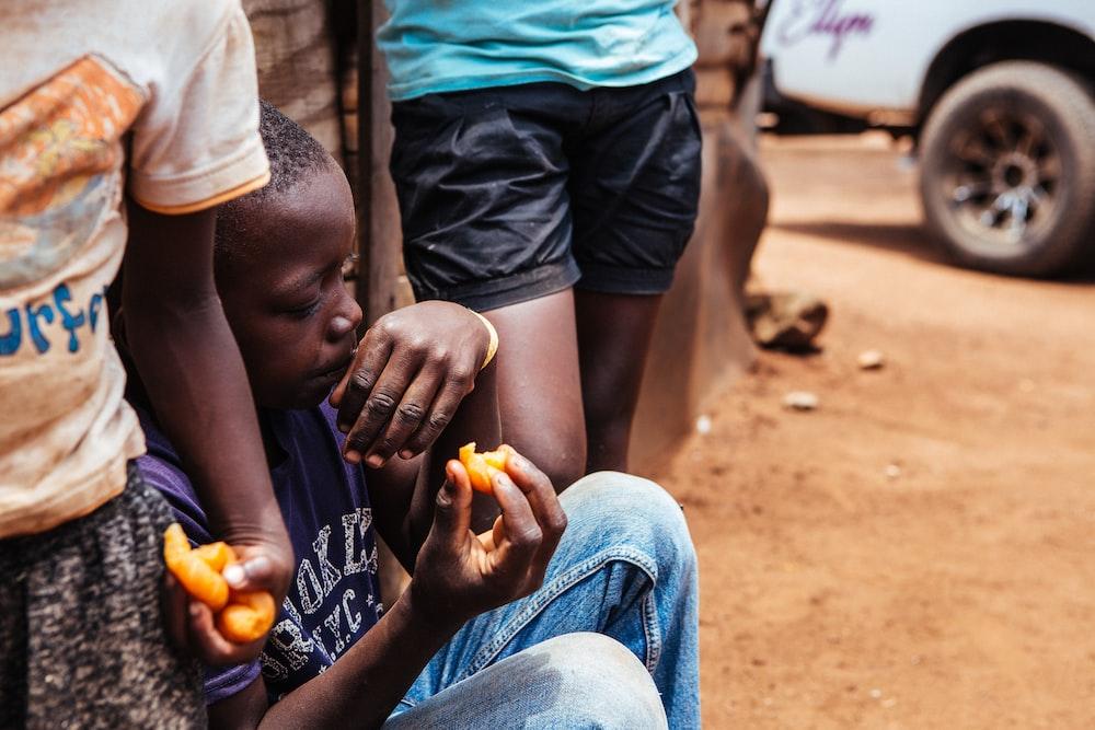 boy sitting while holding food during daytime