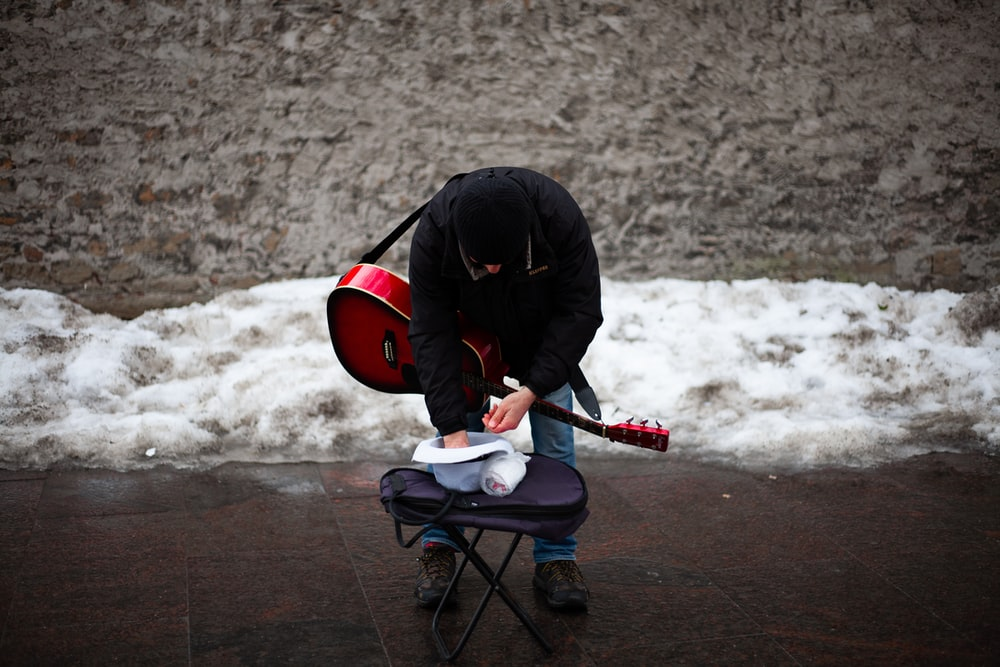 standing man using red and black acoustic guitar