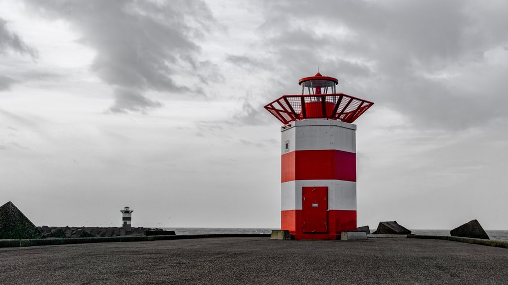 white and red striped lighthouse under white skies