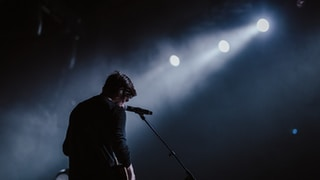 man standing beside black dynamic microphone