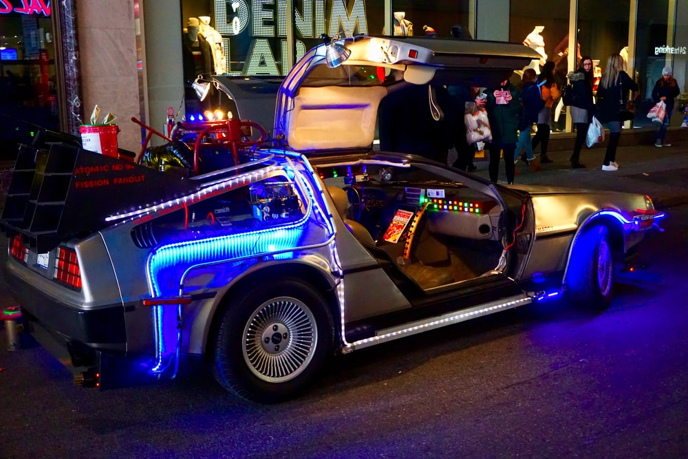 lighted silver gullwing coupe parked on sidewalk