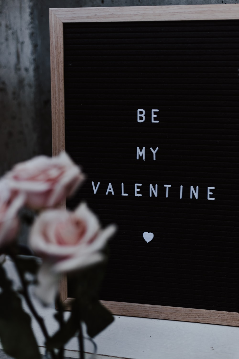 Be my valentine board near pink roses