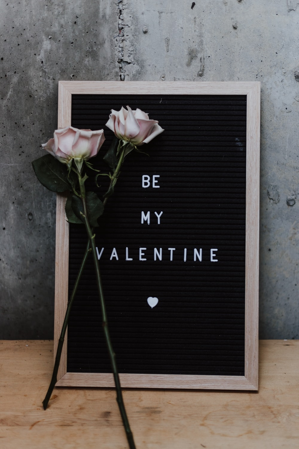 two pink roses learning on be my valentine board