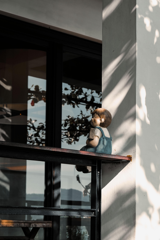 sitting child statuette on railing