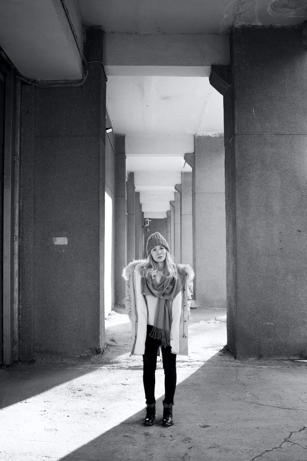 grayscale photography of woman standing near column