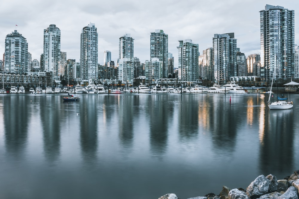 high rise buildings reflected on water during daytime