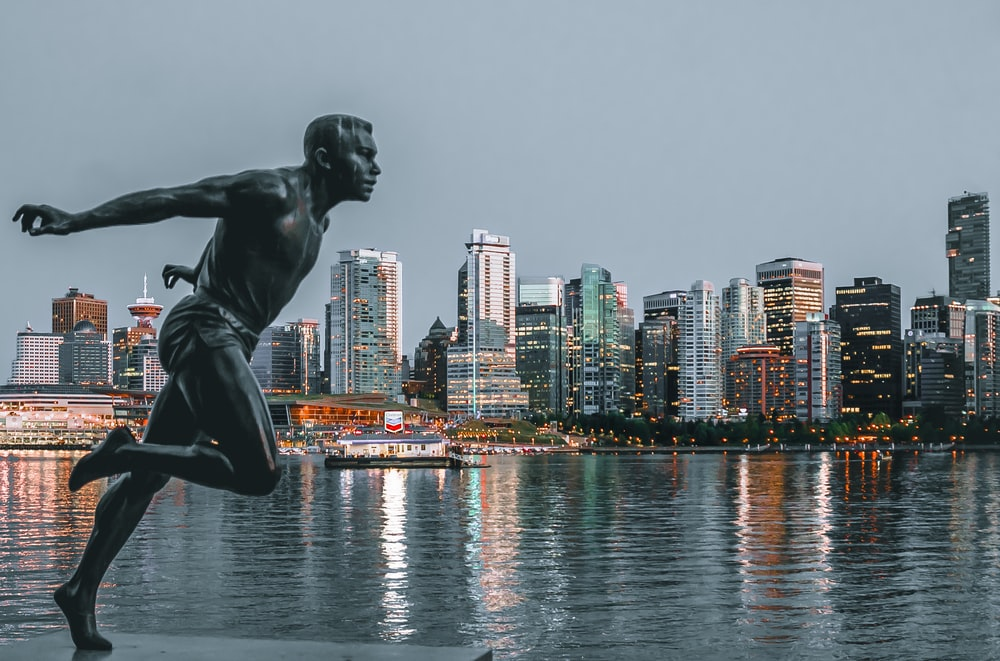 statue of topless man on concrete platform near body of water during daytime