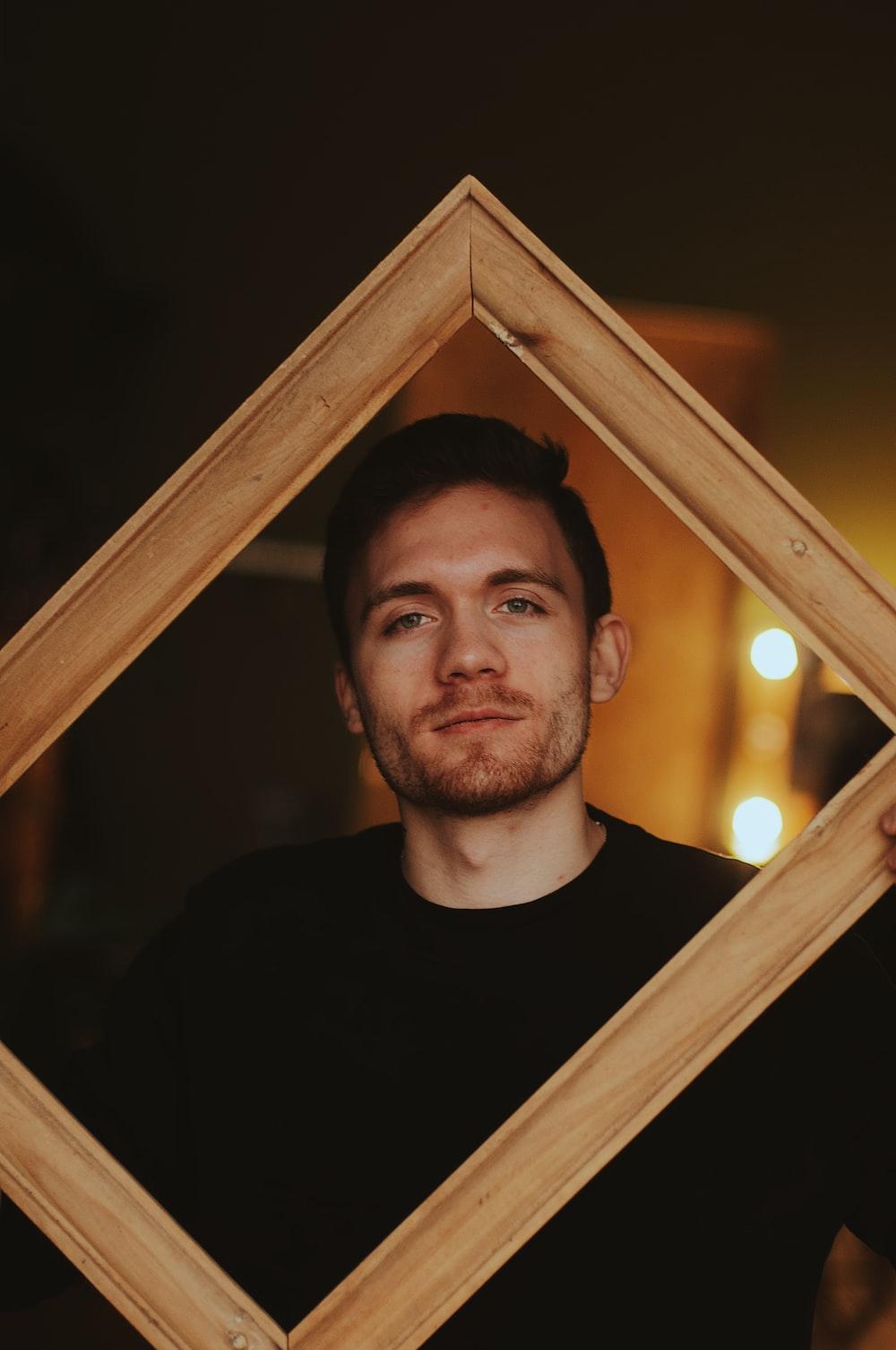 man wearing black shirt holding brown wooden frame
