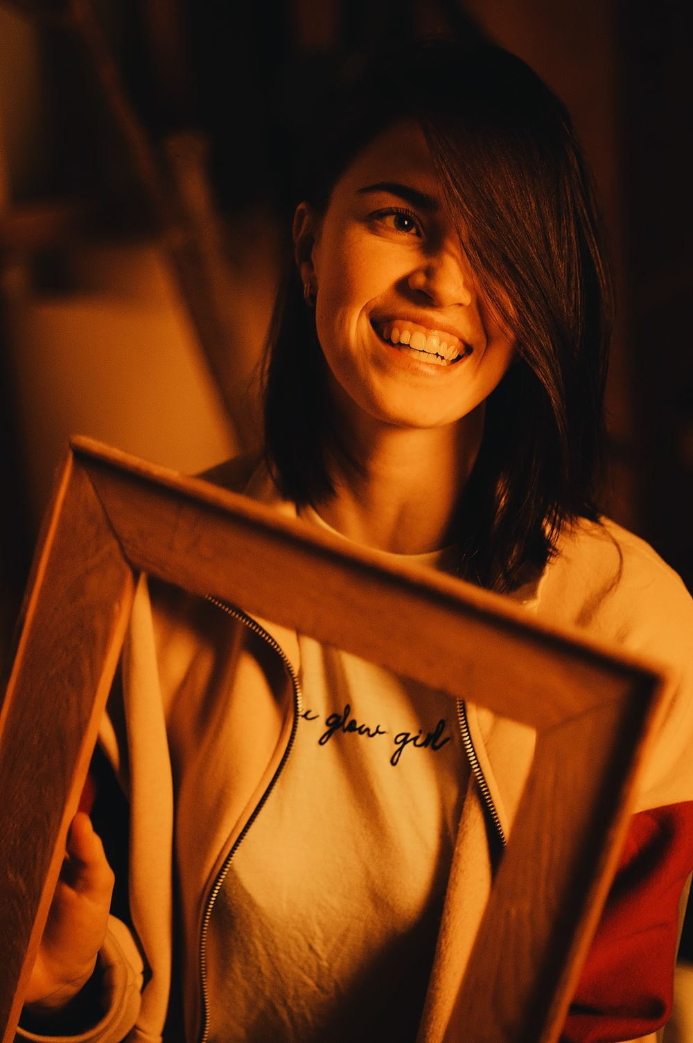 smiling woman holding brown wooden frame