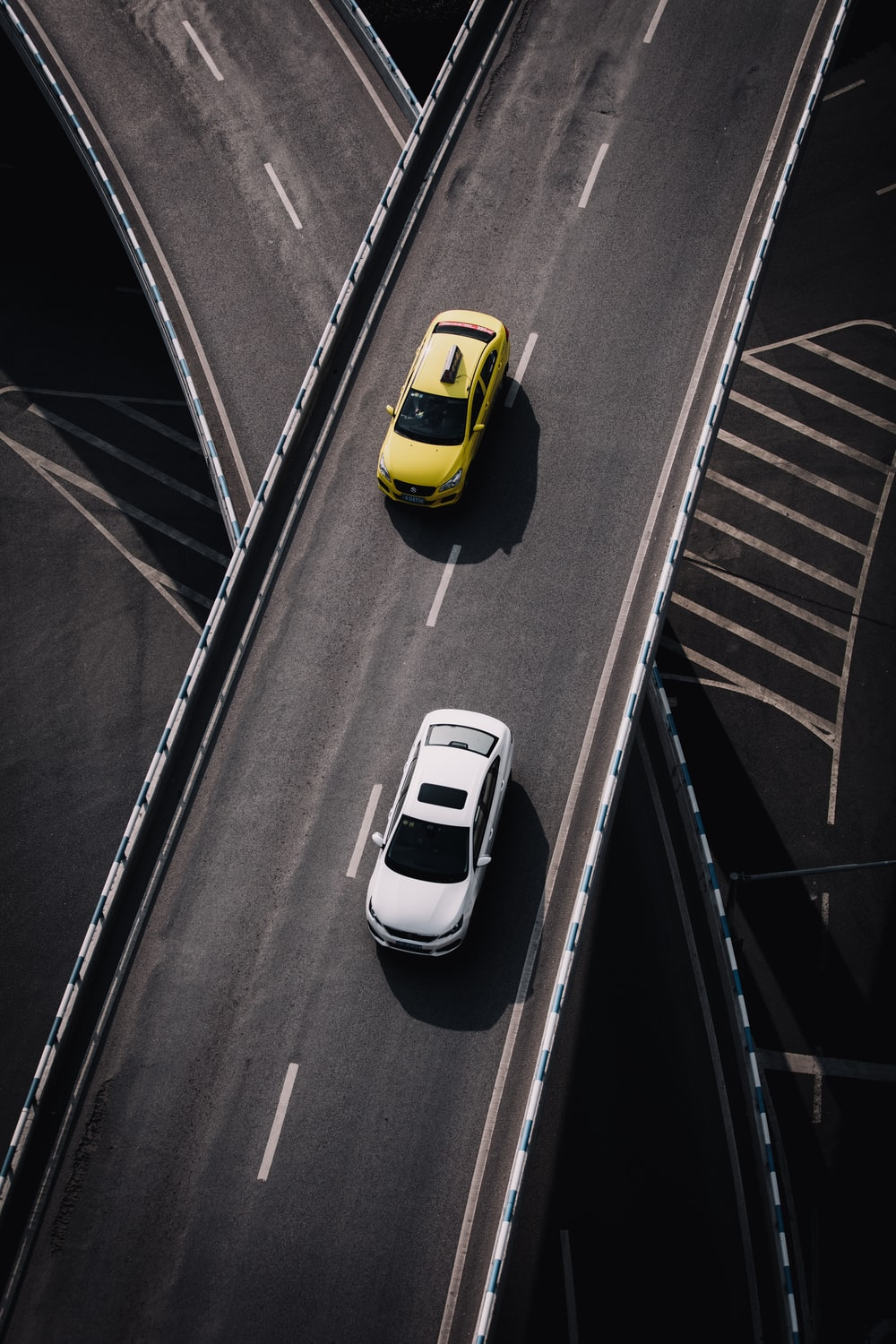 yellow and white vehicles passing on black asphalt road