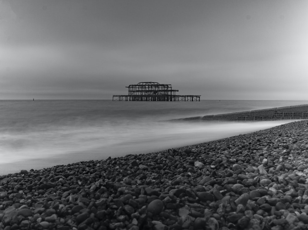 grayscale photography of structure on body of water during daytime