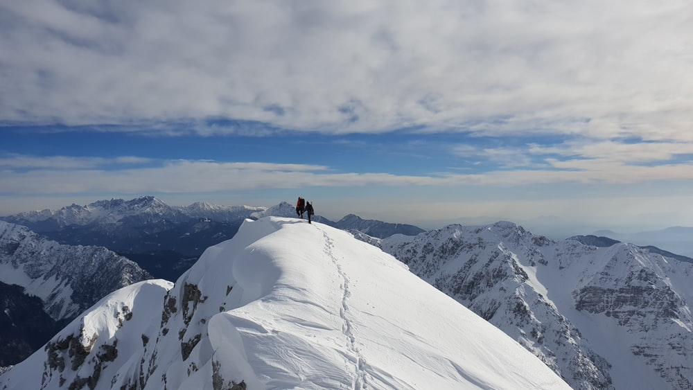 silhouette of person on top of snow-covered mountain under white cloudy sky during daytime
