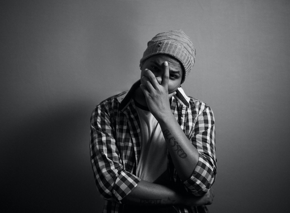 man covering face with left hand