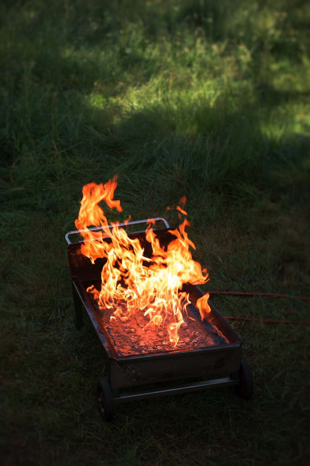 rectangular wheeled grill with fire on lawn during daytime