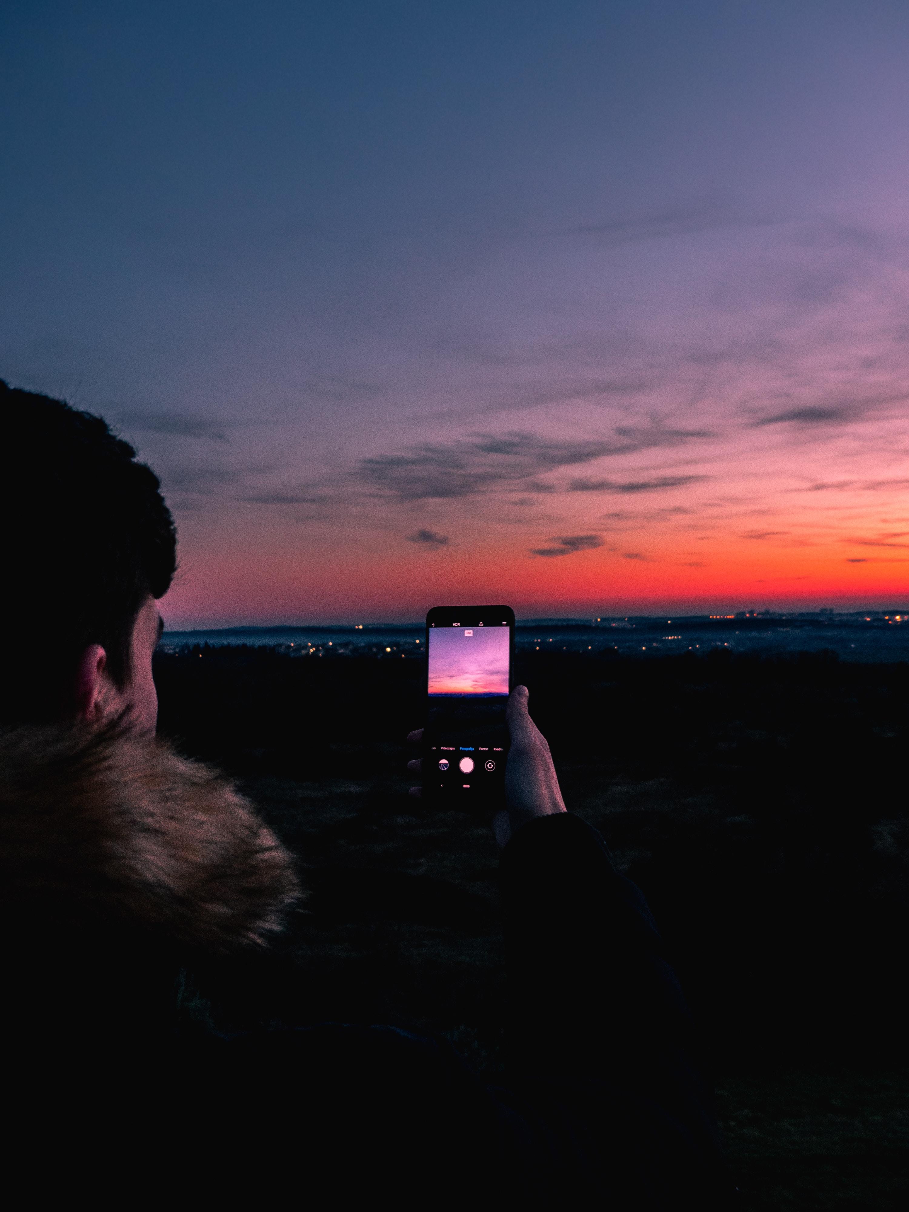 person taking photo of horizon