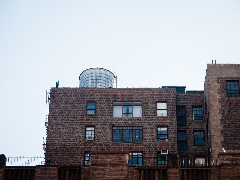 brown brick building with tall water tank behind