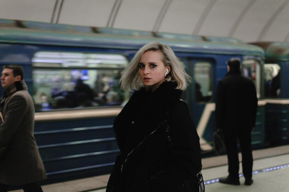 woman wearing black coat near the blue train