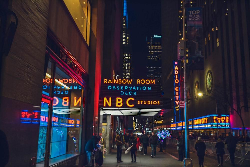 several people walking beside NBC Studios building